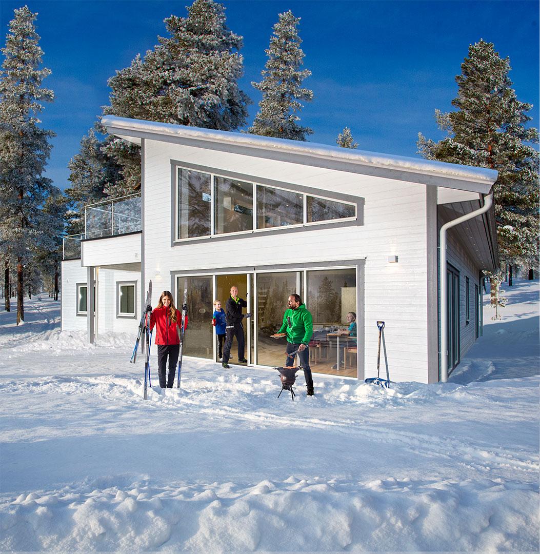 Glaspartier monteras på solklar vinterdag. Skidor och grillning vid huset.
