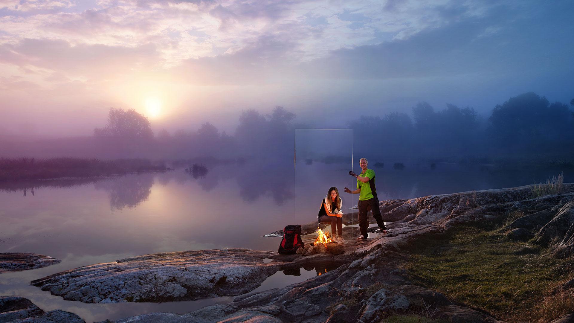 Vacker natur, solnedgång vid stilla vatten och klippor, vid lägereld.